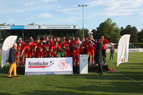 HFV-Präsident Stefan Reuß (re.) übergibt den Krombacher Hessenpokal an die Mannschaft des TSV Steinbach. Fotos: Läpple