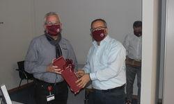 HFV-Mitarbeiter Luigi Urzo (re.) übergibt Gerhard ein Geschenk.