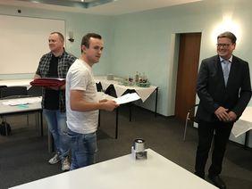 Roland Esch nach der Übergabe der Urkunde an Pascal Urbanski und Marcus Rettig (v.r.)
