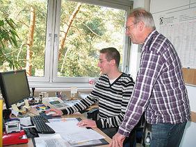 Mit Begeisterung und Spaß bei der Sache: Bernd Kloft arbeitet Stefan Minow (am Computer) ein. Foto: Anne Lange